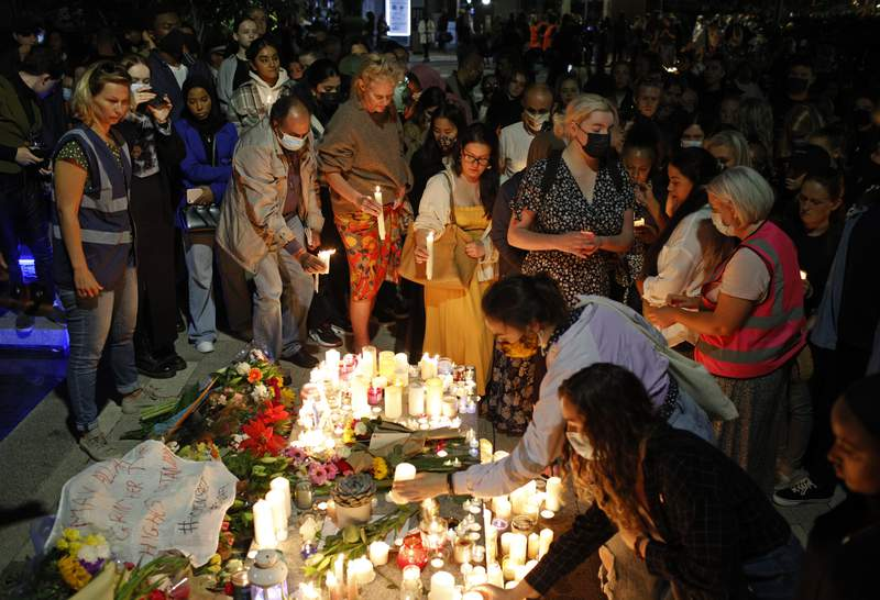 FILE - In this Friday, Sept. 24, 2021 file photo, people line up to place candles during a vigil for murdered 28-year-old teacher Sabina Nessa in Kidbrooke in south-east London. British police charged a 36-year-old man on Monday Sept. 27, 2021, with the murder of Sabina Nessa, a primary school teacher killed as she walked to meet a friend in London. (AP Photo/David Cliff, File)
