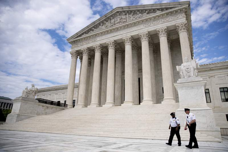 Security officers, one wearing a mask, walk in front of the Supreme Court, Thursday, May 14, 2020, in Washington. (AP Photo/Andrew Harnik)