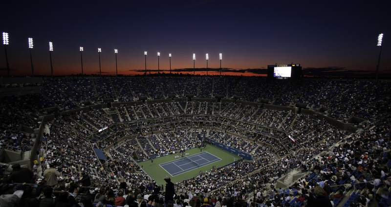 FILE - In this Aug. 31, 2009, file photo, the sun sets over the skyline of New York and Arthur Ashe Stadium during the opening night of the U.S. Open tennis tournament in New York. The mens professional tennis tour is surveying players on LGBTQ issues. ATP CEO Massimo Calvelli tells The Associated Press it is part of a broader initiative to create an environment for players and staff that is inclusive, that is diverse and that is very safe and welcoming. (AP Photo/Amy Sancetta, File)