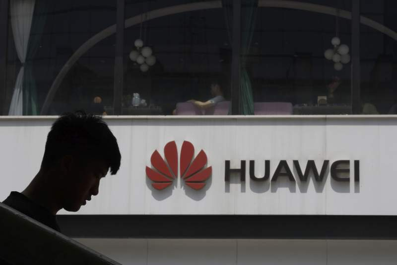 FILE - In this Thursday, May 16, 2019 file photo, a man is silhouetted near the Huawei logo in Beijing. Struggling under U.S. sanctions, Chinese tech giant Huawei has unveiled a new flagship foldable smartphone but says it will only be sold in China.  (AP Photo/Ng Han Guan, File)