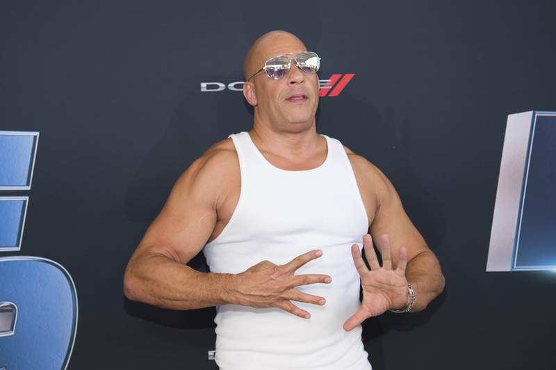 """FILE - In this Jan. 31, 2020 file photo, actor Vin Diesel holds up nine fingers as he attends the the Road to """"Fast & Furious 9"""" Concert inMiami, Fla. Universal Pictures is moving back the release of the ninth Fast and Furious film by a year amid the coronavirus outbreak. The studio on Thursday said that F9 will open on April 2, 2021. It had been previously scheduled to open on May 22, 2020.  The vast majority of people recover from the new virus, but for some, it can cause more severe illness, including pneumonia. (Photo by Scott Roth/Invision/AP, File)"""