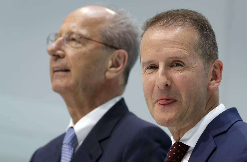 FILE - In this Friday, April 13, 2018, file photo, Herbert Diess, right, CEO of the Volkswagen, and Hans Dieter Poetsch, left, chairman of the board of directors of Volkswagen address the media during a press conference in Wolfsburg, Germany. Volkswagen said charges of securities-law violations against its CEO and board chairman are to be dropped in return for a 9 million-euro ($10 million) payment, removing a potential distraction for the company's management team as it copes with the virus crisis and oversees the rollout of a new generation of electric cars. (AP Photo/Michael Sohn, File)