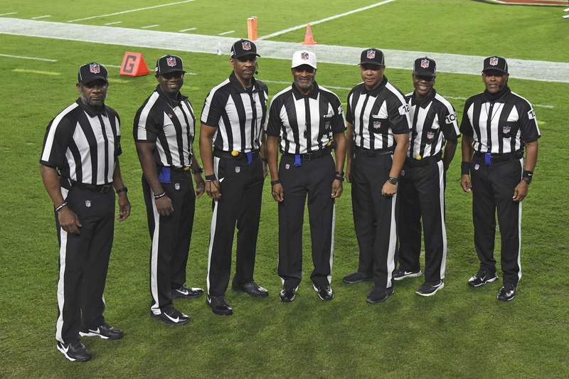 NFL officials, from left, umpire Barry Anderson, side judge Anthony Jeffries, down judge Julian Mapp, referee Jerome Boger, back judge Greg Steed, field judge Dale Shaw (104), line judge Carl Johnson (101) pose for a photo before an NFL football game between the Tampa Bay Buccaneers and the Los Angeles Rams Monday, Nov. 23, 2020, in Tampa, Fla. The game is the first in NFL history to feature an all African-American officiating crew. (AP Photo/Jason Behnken)