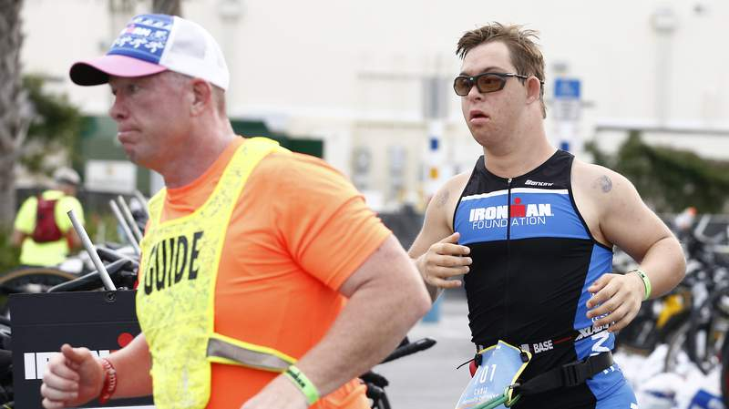 PANAMA CITY BEACH, FLORIDA - NOVEMBER 07: Guide Dan Grieb leads Chris Nikic through the transition from the bike portion to the run portion of IRONMAN Florida on November 07, 2020 in Panama City Beach, Florida. Chris Nikic is attempting to become the first Ironman finisher with Down syndrome. (Photo by Michael Reaves/Getty Images for IRONMAN)