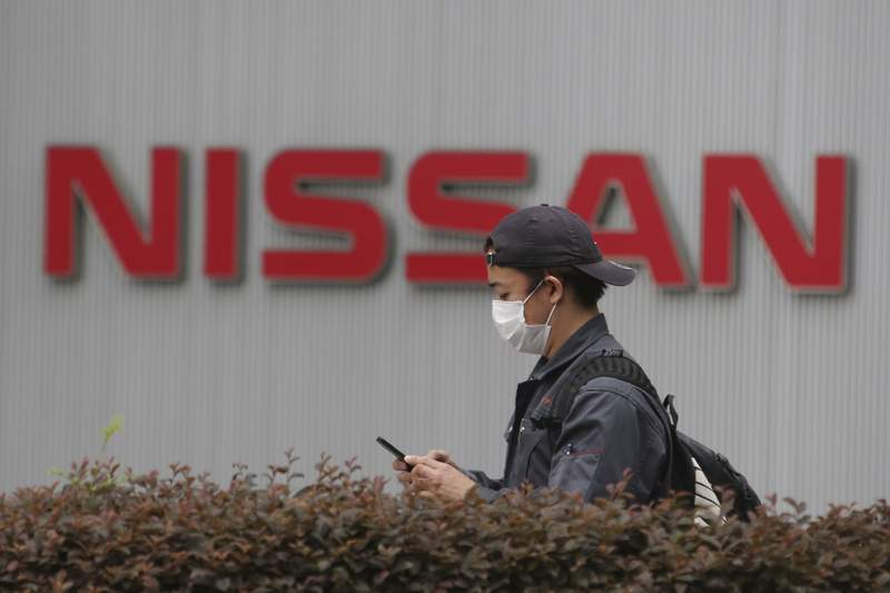 A man walks past the corporate logos at the global headquarters of Nissan Motor Co., Ltd. in Yokohama near Tokyo, Thursday, May 21, 2020. Nissan says it is developing a new way to produce auto parts, highlighting the Japanese automakers engineering finesse, even as it struggles to recover from a scandal centered around its former chairman, Carlos Ghosn. (AP Photo/Koji Sasahara)