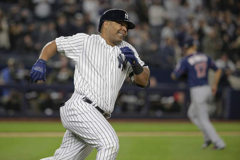 FILE - In this Oct. 4, 2019, file photo, New York Yankees designated hitter Edwin Encarnacin runs down the first base line after hitting a double against the Minnesota Twins during the first inning of Game 1 of a baseball American League Division Series in New York. The Chicago White Sox have agreed to a $12 million, one-year contract with veteran slugger Encarnacin, a person familiar with the negotiations told The Associated Press on Wednesday night. The person spoke on condition of anonymity because the deal has not been announced. Encarnacin is due $11 million in salary next season and a $1 million signing bonus, with the White Sox holding an option for the 2021 season. (AP Photo/Seth Wenig, File)