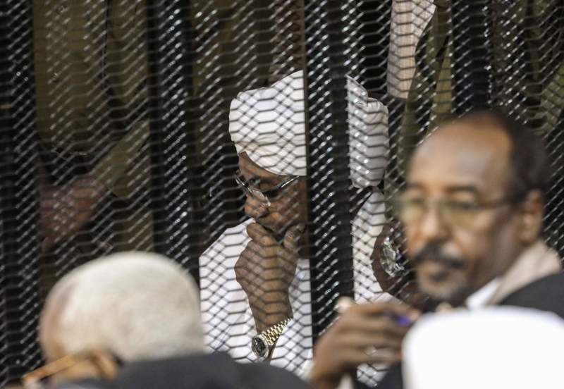 FILE - In this Aug. 24, 2019 file photo, Sudan's autocratic former President Omar al-Bashir sits in a cage during his trial on corruption and money laundering charges, in Khartoum, Sudan. On Tuesday, July 21, 2020, al-Bashir is back in court, this time facing charges of plotting the 1989 Islamist-backed coup that removed an elected government and brought him to power. The trial adjourned until Aug. 11. (AP Photo, File)