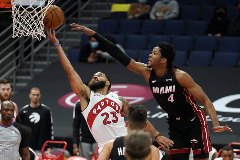 Toronto Raptors guard Fred VanVleet (23) gets fouled by Miami Heat forward KZ Okpala (4) during the first half of an NBA preseason basketball game Friday, Dec. 18, 2020, in Tampa, Fla. The Raptors are playing their home games in Tampa as a result of Canada's strict travel regulations stemming from the coronavirus pandemic. (AP Photo/Chris O'Meara)