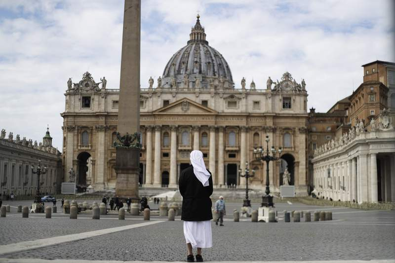A nun stands in St. Peter's Square at the Vatican, Sunday, March 21, 2021. Pope Francis has denounced racism, likening it to a virus that lurks in waiting and continues to be shameful. Francis in a tweet on Sunday called racism a virus that quickly mutates and, instead of disappearing, goes into hiding, and lurks in waiting.  (AP Photo/Gregorio Borgia)