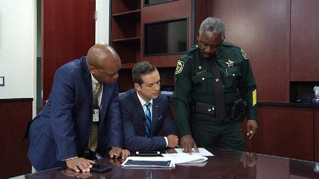 Orange County Sheriff Jerry Demings and public information office Jeff Williamson look over crash numbers with News 6 anchor Matt Austin.