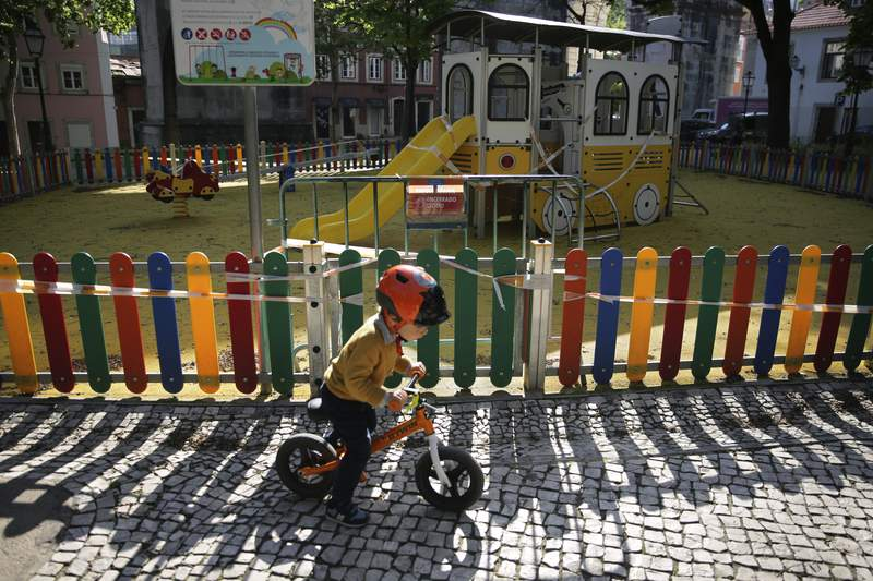 A child rides a bicycle outside a playground closed due to the coronavirus pandemic at a public garden in Lisbon, Wednesday, April 22, 2020. (AP Photo/Armando Franca)