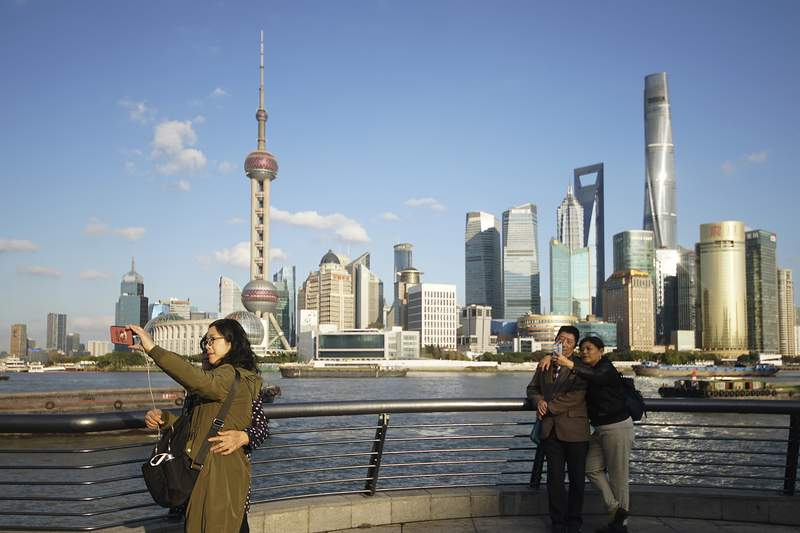FILE - In this Nov. 12, 2020 file photo, people take selfies of the Pudong skyline as they stand on the Bund in Shanghai, China.  A new study finds that cleaner air from the pandemic lockdown warmed the planet a bit in 2020, especially in places such as the eastern United States, Russia and China. Tuesday, Feb. 2, 2021 study found the pandemic lockdown reduced soot and sulfate air pollution, but those particles also reflect the sun's heat and help cool areas briefly. (AP Photo)