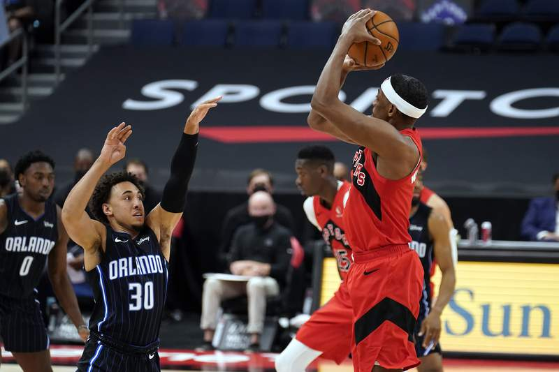 Toronto Raptors guard Paul Watson Jr., (1) puts up a three-point shot over Orlando Magic guard Devin Cannady (30) during the second half of an NBA basketball game Friday, April 16, 2021, in Tampa, Fla. (AP Photo/Chris O'Meara)