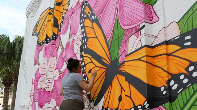 An Ink Dwell artist paints a Migrating Mural on University Blvd. at Full Sail University.