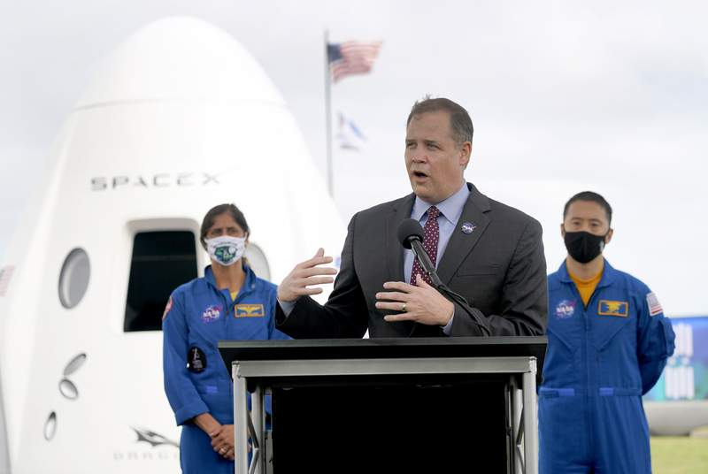 NASA administrator Jim Bridenstine, center, speaks during a news conference with astronauts Suni Williams, back left, and Jonny Kim, in front of a mockup of the SpaceX crew capsule at the Kennedy Space Center in Cape Canaveral, Fla., Friday, Nov. 13, 2020. (AP Photo/John Raoux)