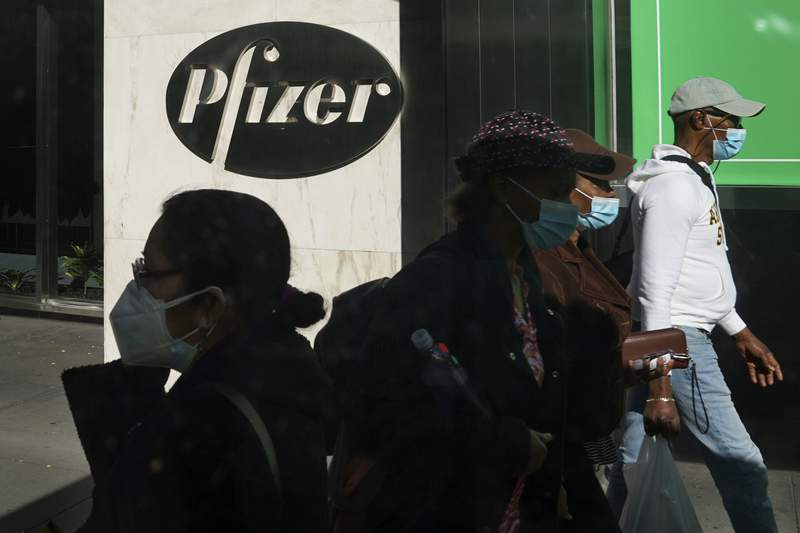 FILE - In this Nov. 9, 2020, file photo, pedestrians walk past Pfizer world headquarters in New York. Pfizer announced Wednesday, Nov. 18, 2020, more results in its ongoing coronavirus vaccine study that suggest the shots are 95% effective a month after the first dose. (AP Photo/Bebeto Matthews, File)