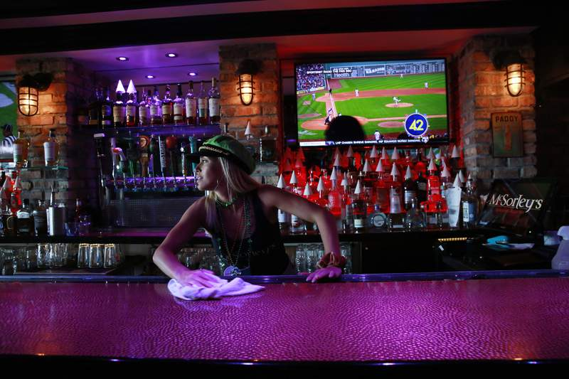 Kelli Rizza cleans the bar before closing the doors of McSorley's Beach Pub at 5 o'clock on Tuesday, March 17, 2020, in Fort Lauderdale Fla. Florida Gov. Ron DeSantis, released a statement saying that all bars and nightclubs throughout Florida will close for the next 30 days. (AP Photo/Brynn Anderson)