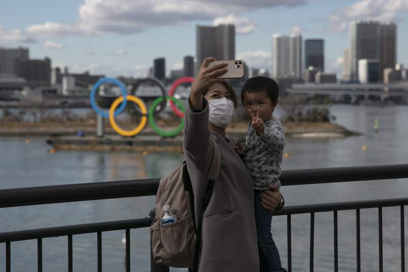 FILE - In this Wednesday, Jan. 29, 2020, file photo, a woman with a young boy takes a selfie with the Olympic rings, in Tokyo's Odaiba district. Tokyo Olympic organizers are trying to shoot down rumors that this summer's games might be cancelled or postponed because of the spread of a new virus. (AP Photo/Jae C. Hong, File)