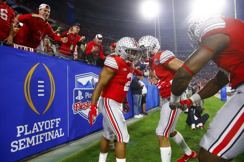 FILE - In this Dec. 28, 2019, file photo, Ohio State running back J.K. Dobbins, left, celebrates his touchdown with wide receiver Austin Mack during the first half of the team's Fiesta Bowl NCAA college football playoff semifinal against Clemson,  in Glendale, Ariz. Clemson is preseason No. 1 in The Associated Press Top 25, Monday, Aug. 24, 2020, a poll featuring nine Big Ten and Pac-12 teams that gives a glimpse at whats already been taken from an uncertain college football fall by the pandemic. Ohio State was a close No. 2. (AP Photo/Ross D. Franklin, File)