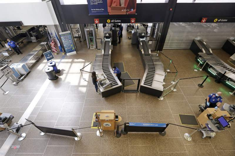 FILE - In this May 18, 2020, file photo, a lone traveler goes through a security check point at Seattle Tacoma International Airport, in SeaTac, Wash. Airports around the country will share $8 billion in federal relief to help them recover from the pandemic. The Federal Aviation Administration announced the grants on Tuesday, June 22, 2021. (AP Photo/Elaine Thompson, File)