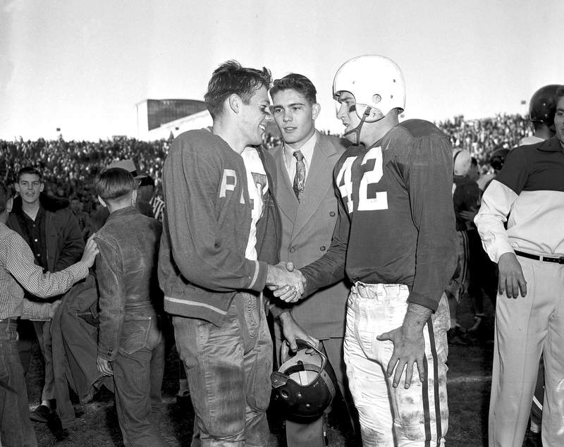 File-This Jan. 1, 1954, file photo shows Alabama fullback Timmy Lewis, right, shaking hands with Rice halfback Dicky Maegle and offers his apologies for coming off the Alabama bench and tackling Maegle on the latter's 95-yard touchdown run during the Cotton Bowl football game in Dallas. Maegle, the Rice running back tackled in the 1954 Cotton Bowl by an Alabama player who came off the bench in one of the most legendary plays in college football history, has died. Rice and the National Football Foundation both said Tuesday, July 6, 2021, that Maegle passed away Sunday. He was 86. (AP Photo/Carl E. Linde, File)