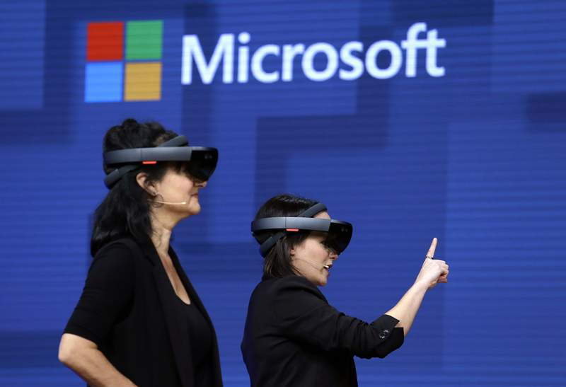 FILE- In this May 11, 2017, file photo, members of a design team at Cirque du Soleil demonstrate use of Microsoft's HoloLens device in helping to virtually design a set at the Microsoft Build 2017 developers conference in Seattle.  Microsoft says it has won a nearly $22 billion contract to supply U.S. Army combat troops with its virtual reality headsets. Microsoft announced the deal Wednesday, March 31, 2021.  (AP Photo/Elaine Thompson, File)