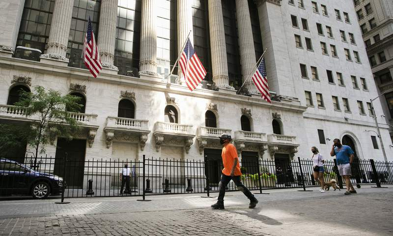 FILE - In this July 21, 2020 file photo, people walk by the New York Stock Exchange. Stocks keep ticking higher on Wall Street, and more gains for the S&P 500 Friday morning, Aug. 28 have it on pace to close out its fifth straight winning week. (AP Photo/Mark Lennihan, File)