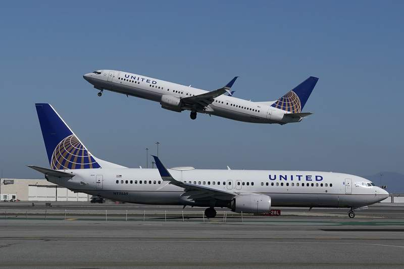FILE - In this Oct. 15, 2020, file photo, a United Airlines airplane takes off over another United plane on the runway at San Francisco International Airport in San Francisco. United Airlines said Wednesday, Jan. 20, 2021, that it finished one of the worst years in its history by losing $1.9 billion in the last three months of 2020, and it predicted more of the same in the first quarter of this year. (AP Photo/Jeff Chiu, File)