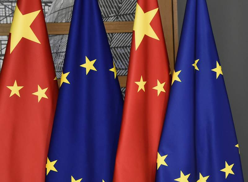 FILE - In this file photo dated Tuesday, Dec. 17, 2019,  EU and Chinese flags at the Europa building in Brussels. Chinas European Union envoy on Wednesday Jan. 27, 2021, is urging the 27-nation European bloc to deepen its ties with his country even further and says he hopes the EUs desire for strategic autonomy will guide its foreign policy in the future .(John Thys/FILE via AP)