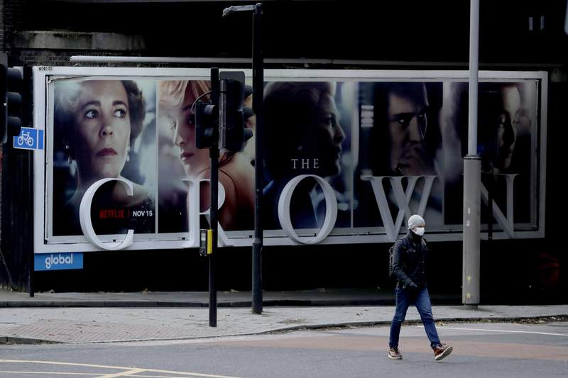 FILE - In this file photo dated Friday, Nov. 20, 2020, a man wearing a face mask walks past a billboard advertising 'The Crown' television series about Britain's Queen Elizabeth II and the royal family, during England's second coronavirus lockdown, in London.  Britains Culture Secretary Oliver Dowden in a newspaper interview published Sunday Nov. 29, 2020, said he thinks The Crown should come with a disclaimer as its a work of fiction with historical liberties taken in the Netflix drama about the British royal family. (AP Photo/Matt Dunham, FILE)