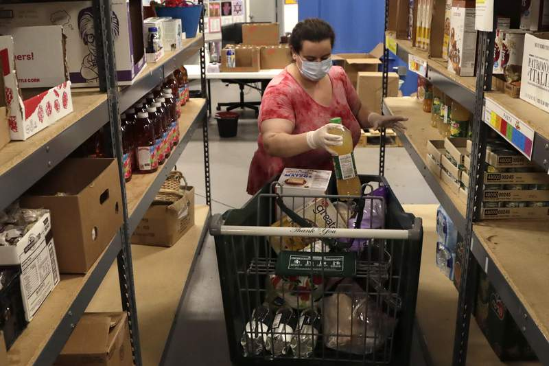 Employee Marie Fernandez wears a protective face mask as she loads a cart with food for a customer at the Jewish Community Services Kosher Food Bank during the new coronavirus pandemic, Wednesday, April 8, 2020, in North Miami Beach, Fla. The food bank has seen a greater need in the community for food since the outbreak of the virus. South Florida synagogues have suspended services and canceled community celebrations. Passover begins Wednesday night and goes for eight days. (AP Photo/Lynne Sladky)