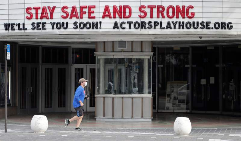 A man wearing a protective face mask jogs past the closed Actors' Playhouse in Coral Gables during Florida's coronavirus lockdown.