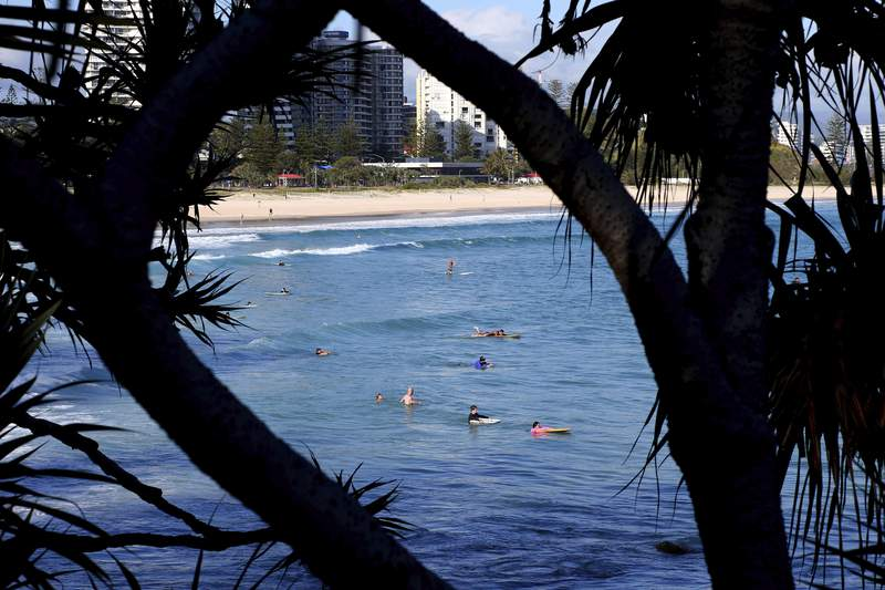 Surfers wade in the water waiting for waves off the Southern Gold Coast area of Greenmount Beach, Gold Coast, Friday, Dec. 15, 2017. A shark fatally mauled a man on Tuesday on Australias Gold Coast city tourist strip, an official said. (David Clark/AAP via AP)