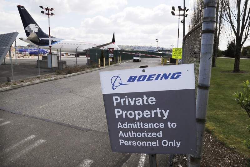 FILE - In this April 20, 2020, file photo, planes sit parked behind a sign marking Boeing property at a Boeing production plant in Renton, Wash. Boeing shareholders approved a slate of 12 company-backed nominees for the board on Monday, April 27, despite recommendations from two proxy advisers against five directors, including the chairman, for what the advisers called poor oversight of the company's handling of the 737 Max crisis.  (AP Photo/Elaine Thompson, File)