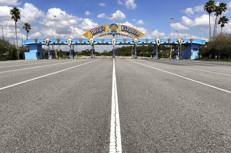 FILE - This March 24, 2020, file photo shows the parking plaza entrance to the Magic Kingdom as Walt Disney World enters its second week of being shut down in response to the coronavirus pandemic. Despite a huge surge of Floridians testing positive for the new coronavirus in recent weeks, Magic Kingdom and Animal Kingdom, two of Disney World's four parks are reopening Saturday, July 11. (Joe Burbank/Orlando Sentinel via AP, File)