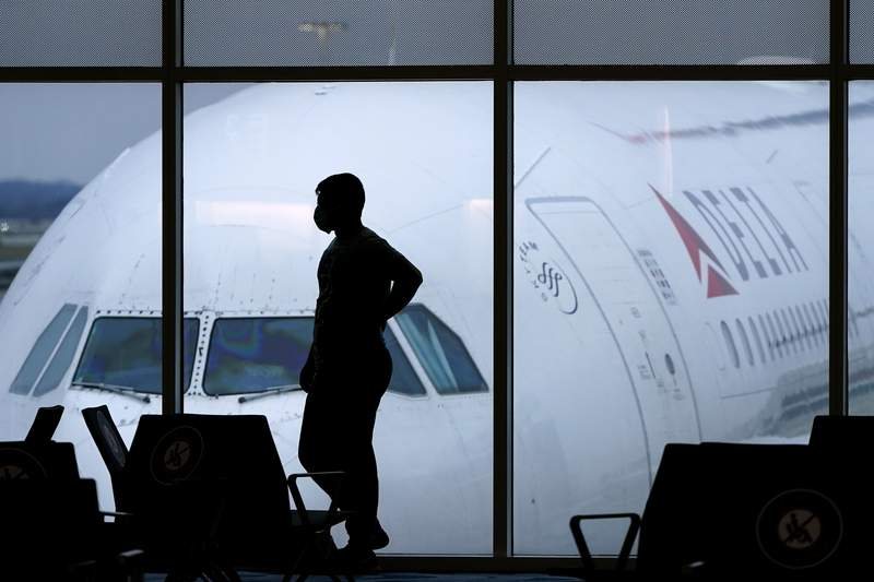 FILE - In this Feb. 18, 2021, file photo, a passenger wears a face mask to help prevent against the spread of the coronavirus as he waits for a Delta Airlines flight at Hartsfield-Jackson International Airport in Atlanta. (AP Photo/Charlie Riedel, File)