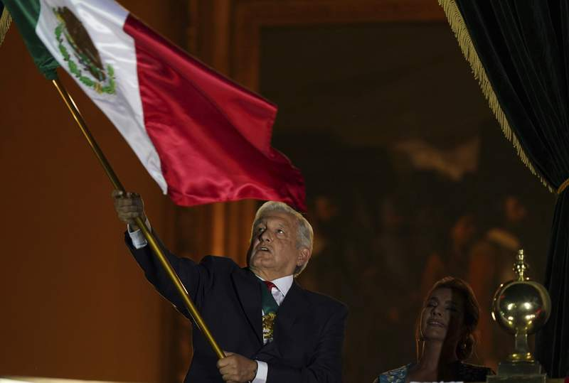 Mexican President Andres Manuel Lopez Obrador waves the national flag after giving the annual independence shout from the balcony of the National Palace to kick off subdued Independence Day celebrations amid the ongoing coronavirus pandemic, at the Zocalo in Mexico City, Wednesday, Sept. 15, 2021. (AP Photo/Fernando Llano)