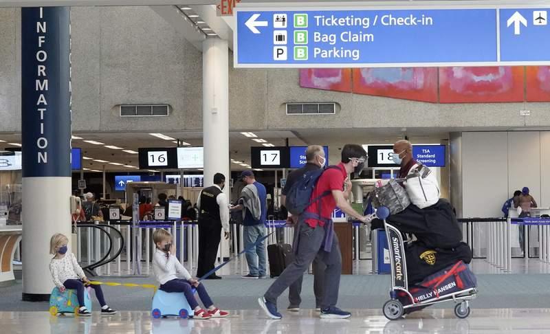 Holiday travelers make their way through Orlando International Airport Tuesday, Nov. 24, 2020, in Orlando, Fla. (AP Photo/John Raoux)