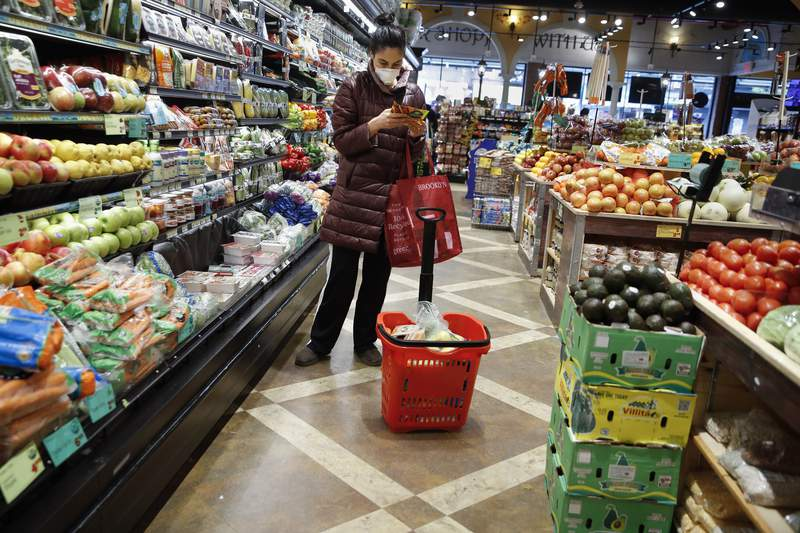 A shopper wears a face mask in the produce section of a grocery store Saturday, April 18, 2020, in the Harlem neighborhood of the Manhattan borough of New York, during the coronavirus outbreak. (AP Photo/John Minchillo)