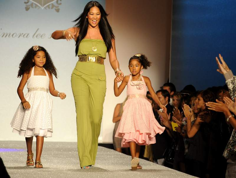 Kimora Lee Simmons acknowledges the applause with her daughters Ming, left, and Aoki, following the showing of her spring 2009 Baby Phat collection during Fashion Week in New York, Friday, Sept. 12, 2008.