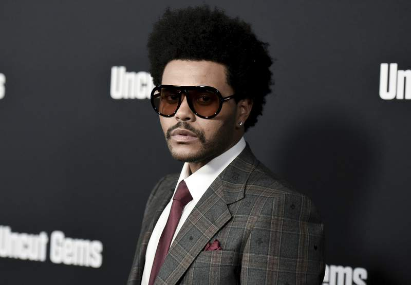 """FILE - The Weeknd attends the LA premiere of """"Uncut Gems"""" at ArcLight Hollywood on Wednesday, Dec. 11, 2019, in Los Angeles. The Weeknd angrily slammed the Grammys, calling the collective corrupt after the pop star received zero nominations despite having multiple hits this year. The three-time Grammy winner criticized the Recording Academy on Tuesday after he was severely snubbed after having one of the years biggest albums with After Hours and being tapped as the Super Bowl halftime headline performer. (Photo by Richard Shotwell/Invision/AP, File)"""