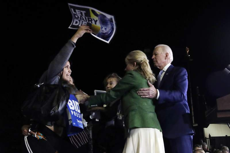 A protester at left, is held back by Jill Biden, center, and her husband Democratic presidential candidate former Vice President Joe Biden, right, during a primary election night rally Tuesday, March 3, 2020, in Los Angeles. (AP Photo/Marcio Jose Sanchez)