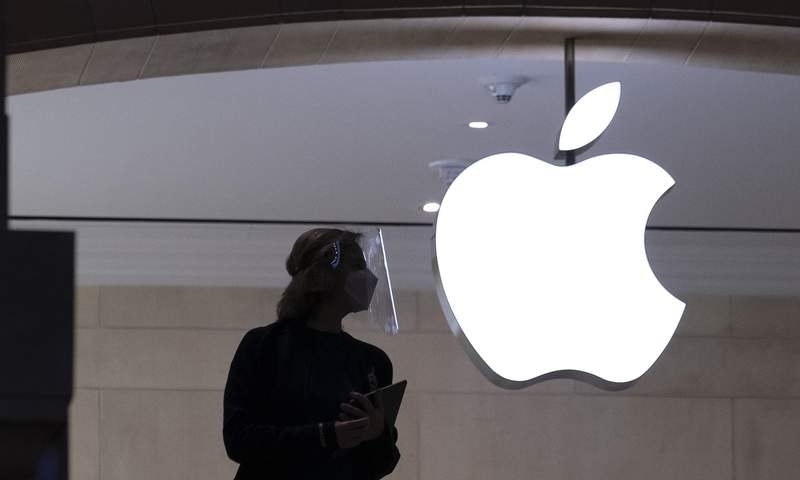 In this Feb. 5, 2021 photo, an Apple store employee is shown in New York. Apple on Wednesday, Sept. 1, is relaxing rules to allow some app developers such as Spotify, Netflix and digital publishers to include an outside link so users can sign up for paid subscription accounts.  (AP Photo/Mark Lennihan)