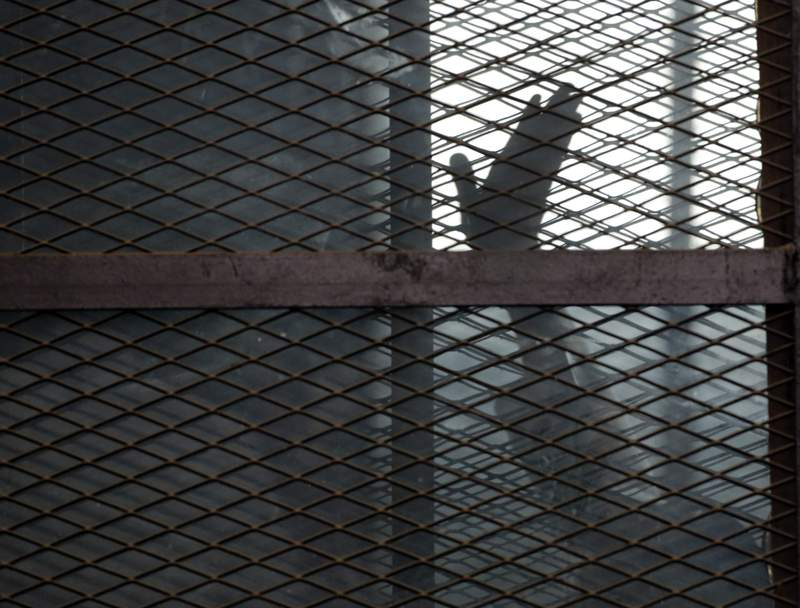 FILE - In this Aug. 22, 2015 file photo, a Muslim Brotherhood member waves his hand from a defendants cage in a courtroom in Torah prison, southern Cairo, Egypt. A leading human rights group says the coronavirus has struck several Egyptian prisons and killed several detainees, as authorities seek to stifle news of the viruss spread behind bars. Human Rights Watch, released an extensive report Monday, July 20, 2020 documenting multiple cases of detainees who died after experiencing virus symptoms without being tested or receiving adequate medical treatment. (AP Photo/Amr Nabil, File)