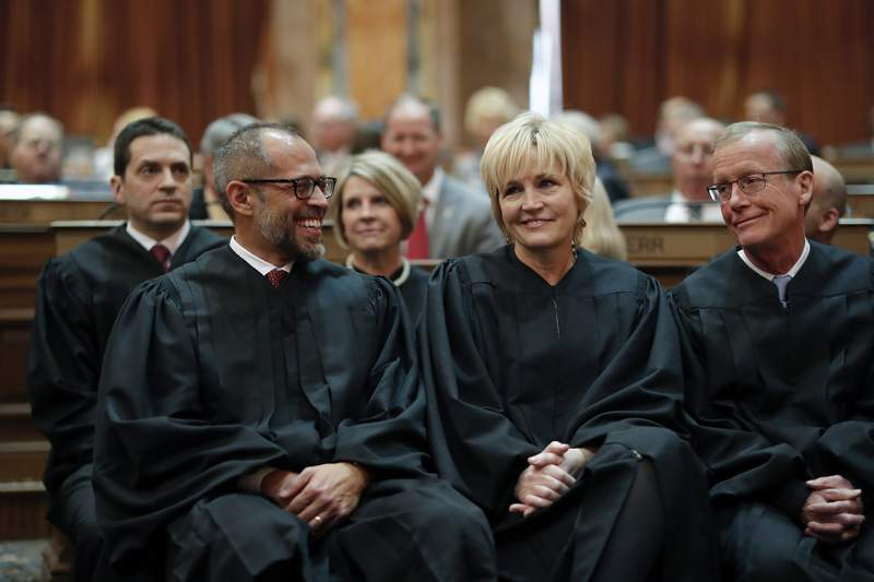 FILE - In this Jan. 14, 2020 file photo, Iowa Supreme Court Justices Christopher McDonald, left, Susan Christensen, center, and Edward Mansfield, right, attend Iowa Gov. Kim Reynolds' Condition of the State address at the Statehouse in Des Moines, Iowa. A divided Iowa Supreme Courton Friday, June 18, 2021,banned police from searching people's uncollected trash without a warrant, outlawing an investigative technique that had been used fordecades. The court ruled 4-3 that officers commit an unreasonable search and seizure under the Iowa Constitution whenthey search for evidence of crimes in trash left for collection outside homes. (AP Photo/Matthew Putney, File)
