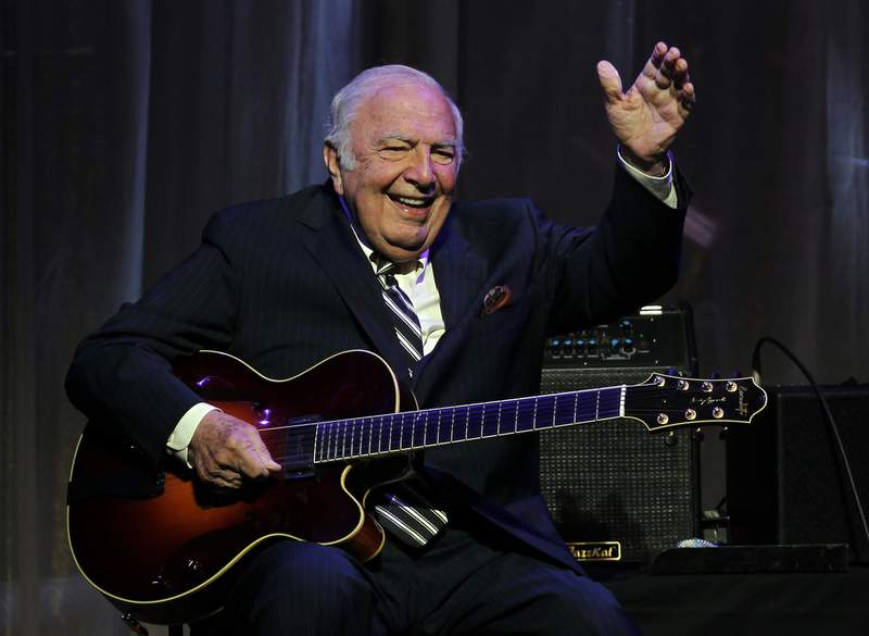 """FILE - This June 5, 2011 file photo shows jazz great John """"Bucky"""" Pizzarelli after being inducted into the New Jersey Hall of Fame during the induction ceremony in Newark, N.J. The virtuoso who performed mostly modern interpretations from the Great American Songbook died on Wednesday, April 1, 2020, in his home in Saddle River, N.J., at the age of 94. (AP Photo/Rich Schultz, File)"""