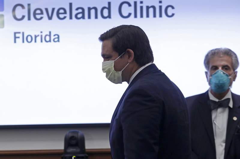 Florida Gov. Ron DeSantis wears a protective mask as he arrives for a news conference at the Cleveland Clinic Florida during the new coronavirus pandemic, Saturday, April 25, 2020, in Weston, Fla. (AP Photo/Lynne Sladky)