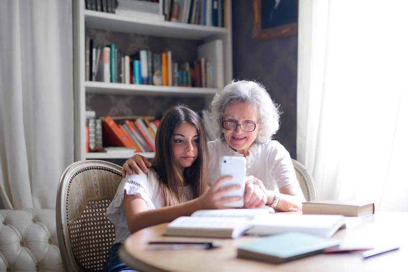 A girl and her grandmother take a photo together.