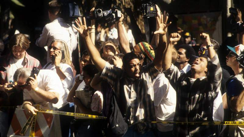 The crowd cheers after hearing the descision of the O.J. Simpson verdict at the Los Angeles Courthouse on October 3, 1995 in Los Angeles, California. Photo by Michael Montfort/Michael Ochs Archives/